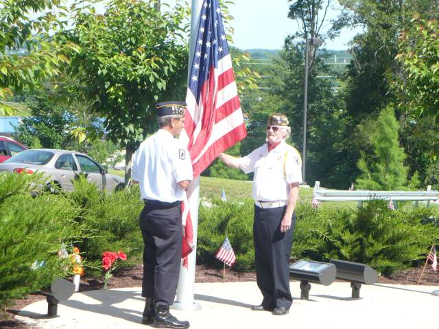 American Legion Post 177 Commander Mark Schmiedeskamp and VFW Post 5468 member Rich Sax preparing to raise the Colors.